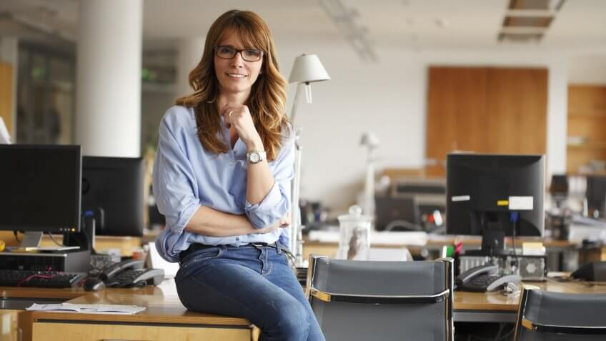 successful woman sitting on desk in office