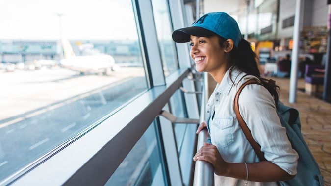 traveling girl with backpack waiting for adventure in airport