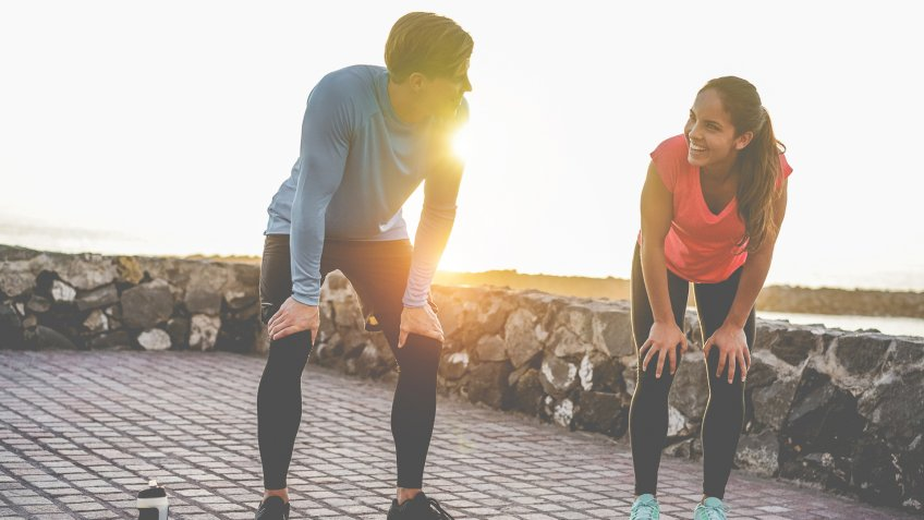 Fit couple taking a rest after fast running workout - Joggers training outdoor at sunset together - Main focus on girl face - Fitness, sport, wellness, workout, gym and healthy lifestyle.