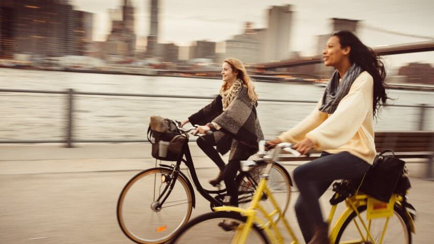 Two girl friends riding their bicycles along The East River in New York City.
