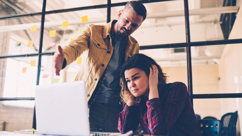 Female student feeling upset with project failure listening to coach critics during meeting in office, irritated leader of company checking work of employee angry about bad ideas and accountings - Image.
