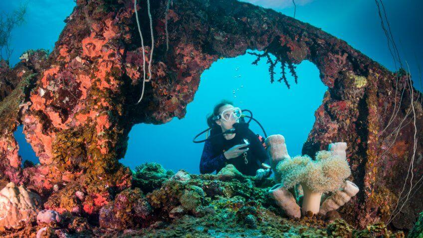 A female diver exploring the wreck Teshio Maru a Japanese Army Cargo Ship with 321 feet (98) on it's length, and was built in 1942-1944.