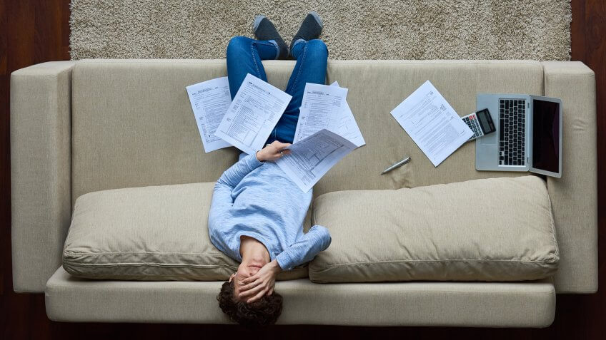 Failed woman leaning on sofa and covering face with hand, she holding business document.