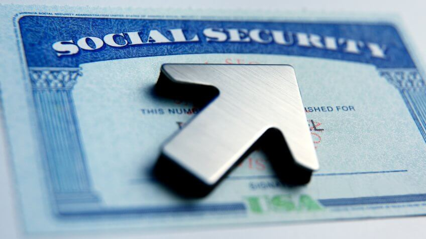 An upwardly pointing arrow rests on top of a social security card.