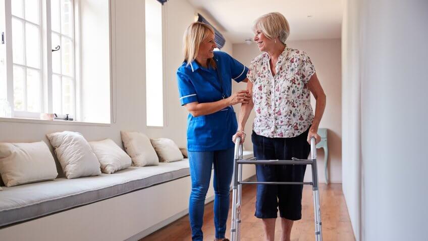 Nurse helping senior woman use a walking frame.