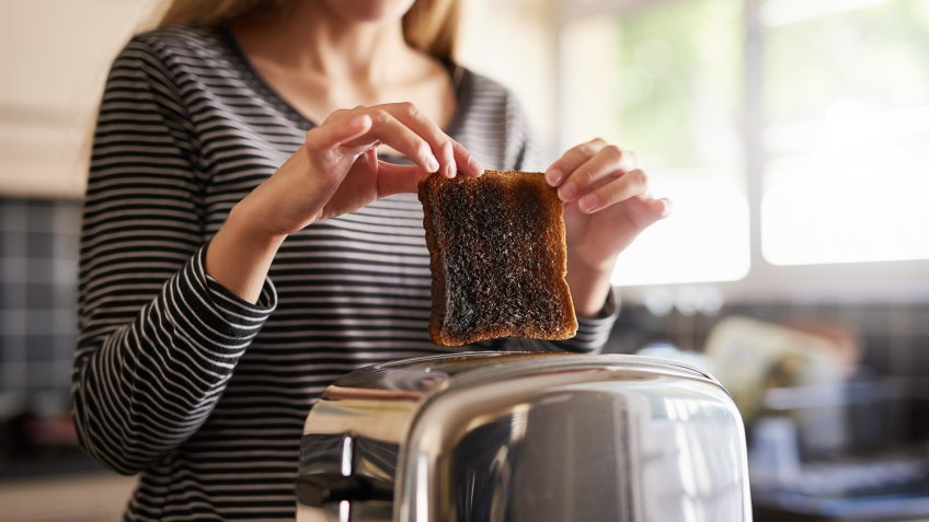 Shot of a woman removing a slice of burnt toast from a toaster at home.