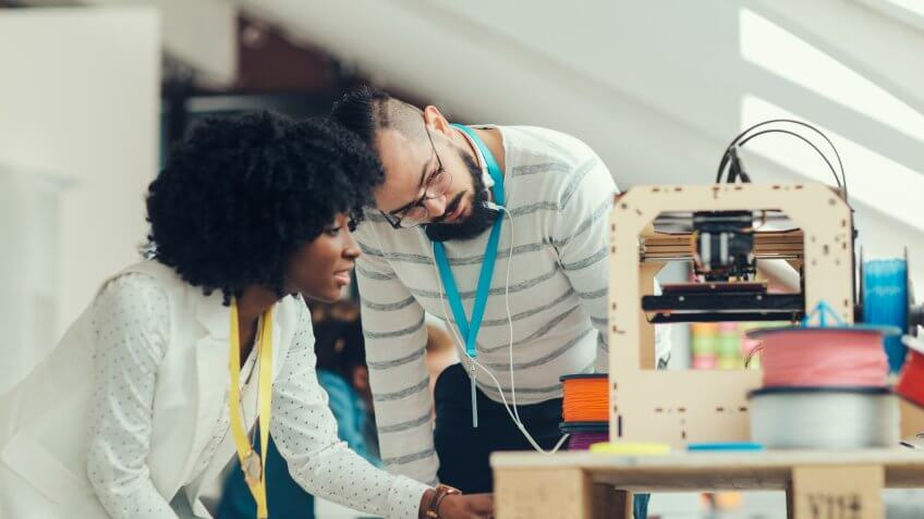 Creative Multi-Ethnic start-up business team working by 3D printer.