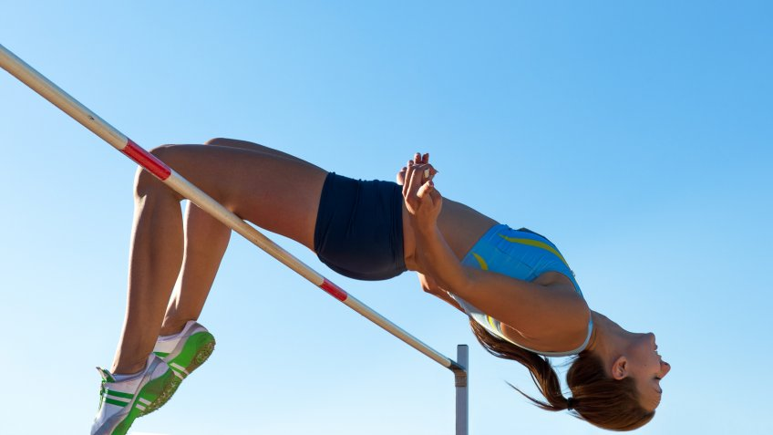Side view of young female athlete jumping over the lath, against the sunlight.