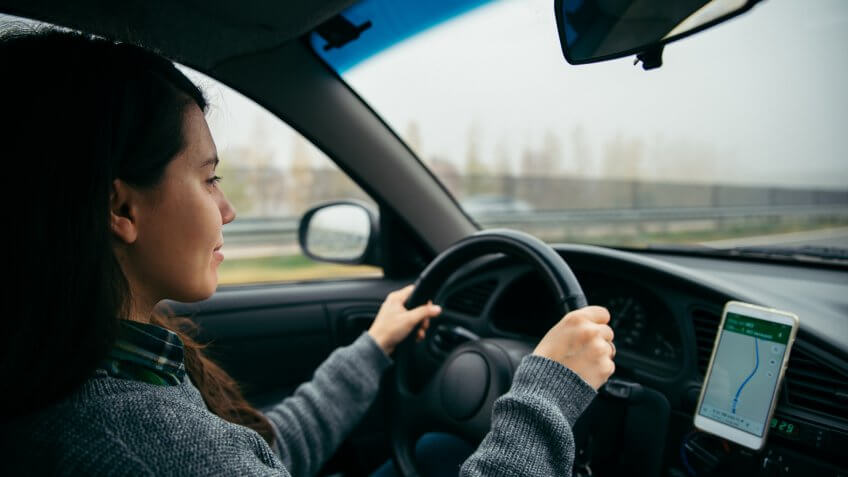 woman driving car by highway in foggy time using navigation on her phone.