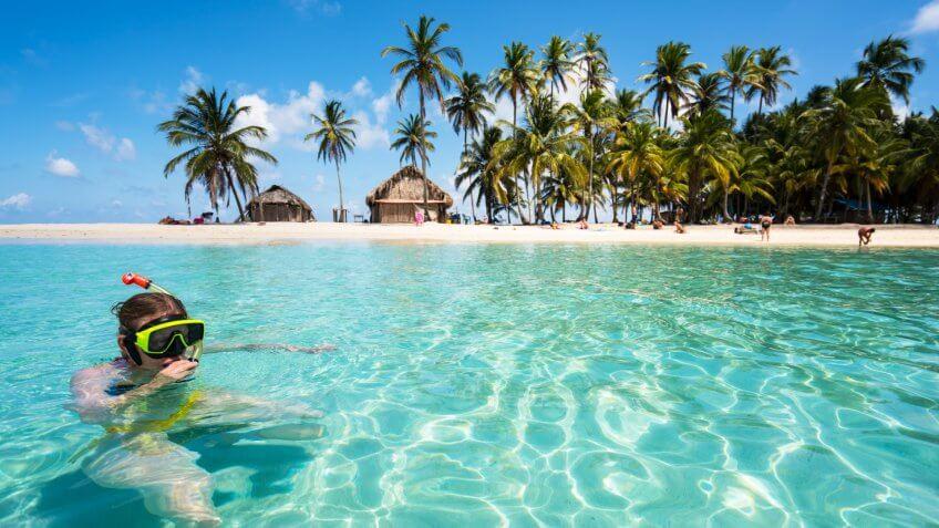 On nice sunny day, Senior woman enjoying sea water on shipwreck close to Island Isla de Perro on San Blas archipelagos in Caribbean See, Panama.