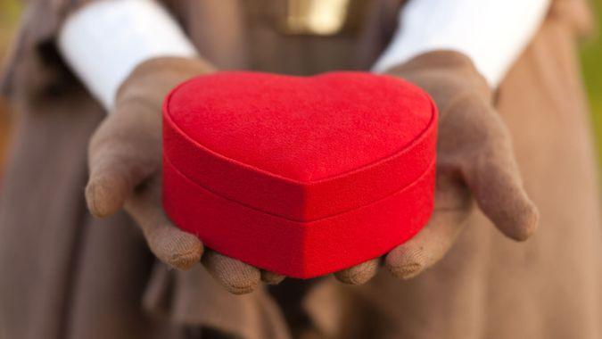 woman holding heart shape box.