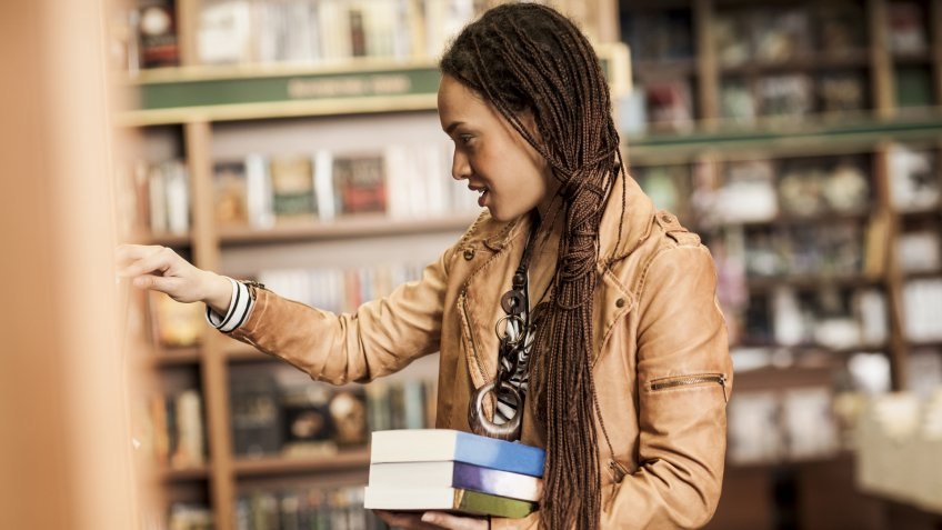 Young woman buying books at a bookstore.
