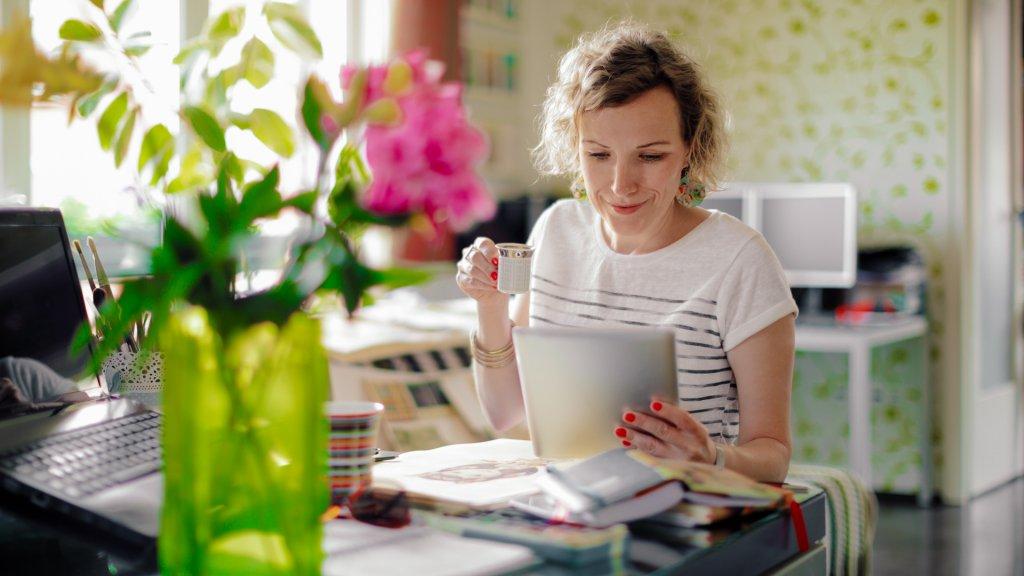 woman looking at digital tablet at home