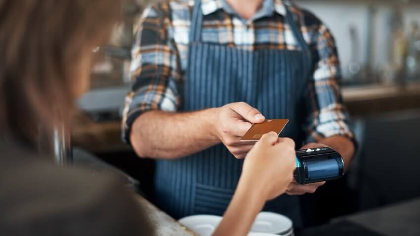 Closeup shot of a unrecognizable person giving a barman a credit card as payment inside of a restaurant.