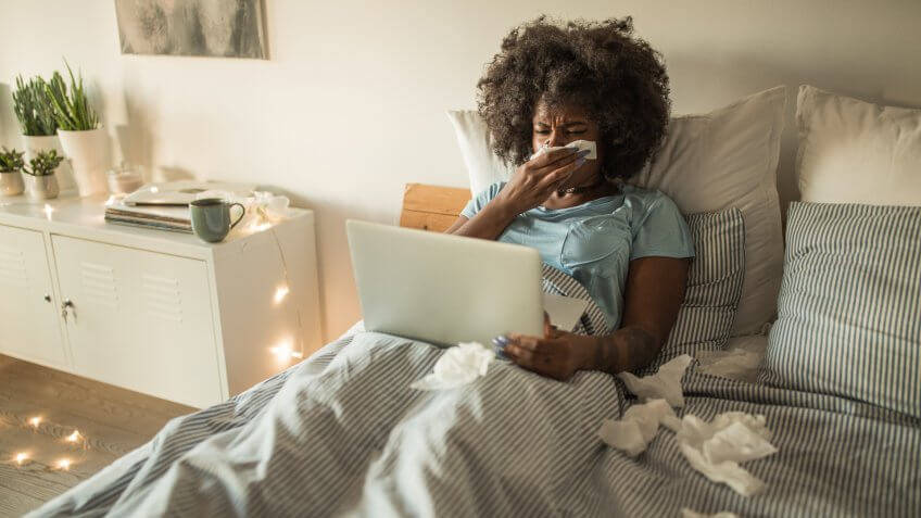 Young African-American woman feeling sick at home.