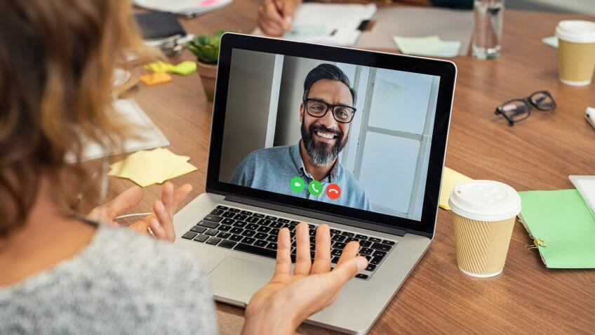 Portrait of smiling man video conferencing on laptop with businesswoman