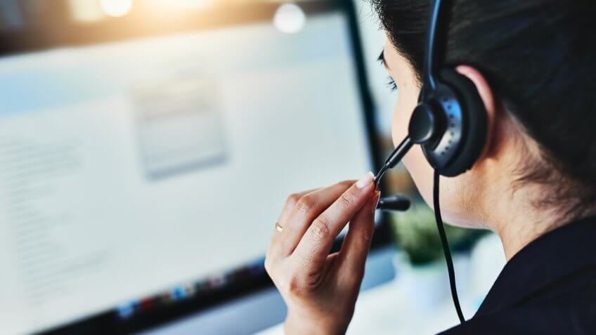 Rearview shot of a young woman working in a call centre.