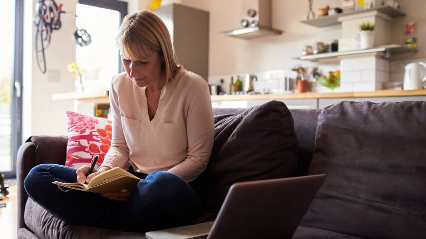Woman Working From Home On Laptop In Modern Apartment.