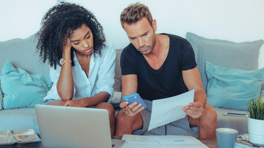 """Young interracial couple in the couch stressed with financial problems doing calculations with paper work""""n."""