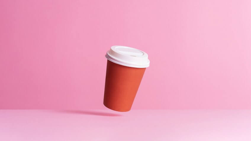 Disposable coffee cup in the air over pink background
