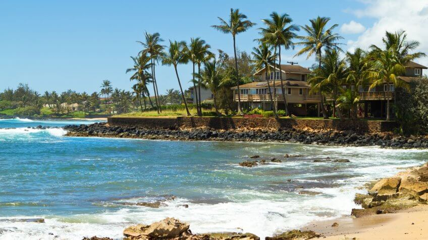 """""""House surrounded by tall palm trees facing the beautiful blue ocean and a sandy beach at south shore of Kauai, Hawaii on a gorgeous sunny, summer day in the tropicsCheck out my Hawaiian Lightbox with more images:""""."""