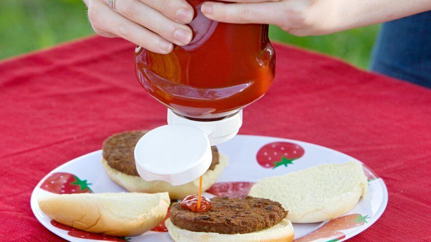 Close-up of Person Putting Ketchup on Hamburger