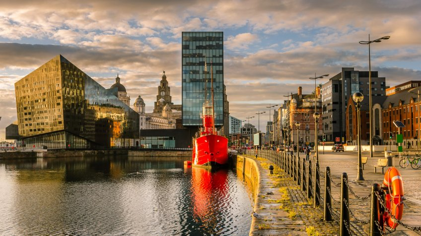 Liverpool's historic waterfront with modern and old architecture at sunset.