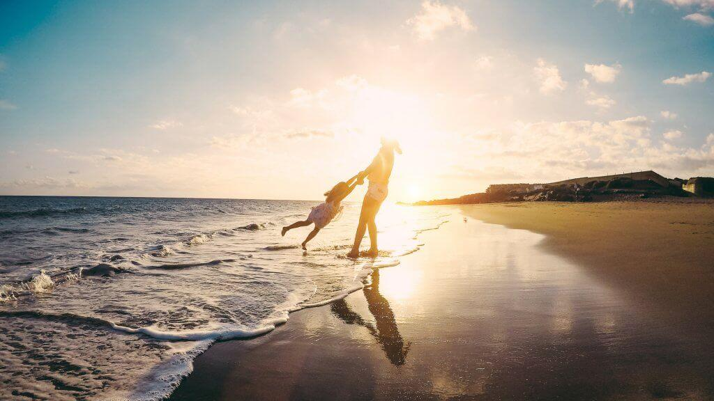 Mother and daughter having fun on tropical beach - Mum playing with her kid in holiday vacation next to the ocean - Family lifestyle and love concept - Focus on silhouettes.