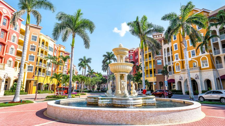 Naples, USA - April 30, 2018: Bayfront condos, condominiums colorful, multicolored, multi-colored buildings with fountain, water, palm trees, blue sky in residential community.