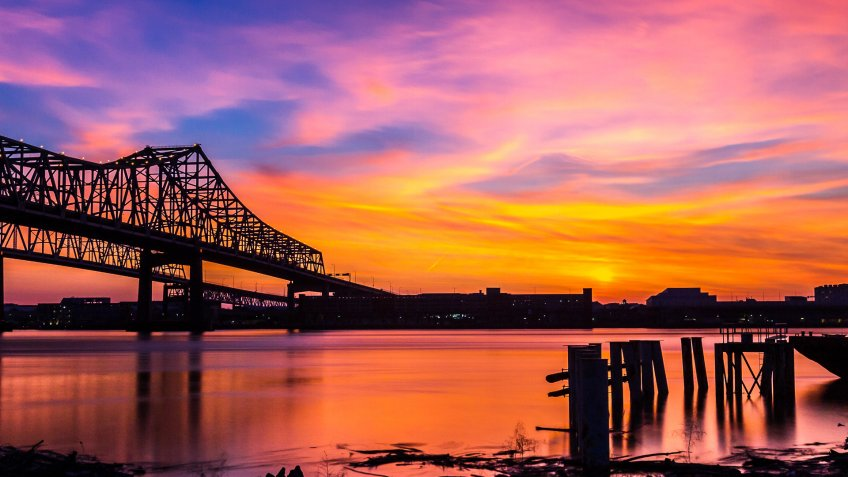 Silhouette of the Crescent City Connection and the City of New Orleans, USA over the Mississippi River during Sunset.