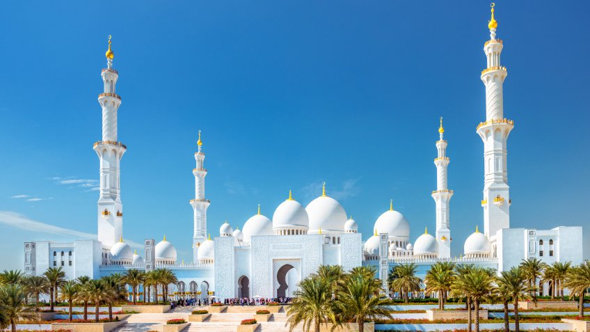 The Sheikh Zayed Grand Mosque Abu Dhabi (UAE) on a beautiful November day with large groups of unrecognizable tourists.
