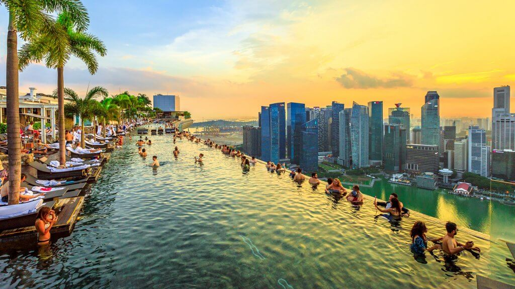 Infinity Pool at sunset of Skypark that tops the Marina Bay Sands Hotel and Casino from rooftop of La Vie Club Lounge on 57th floor. Financial district skyline on background