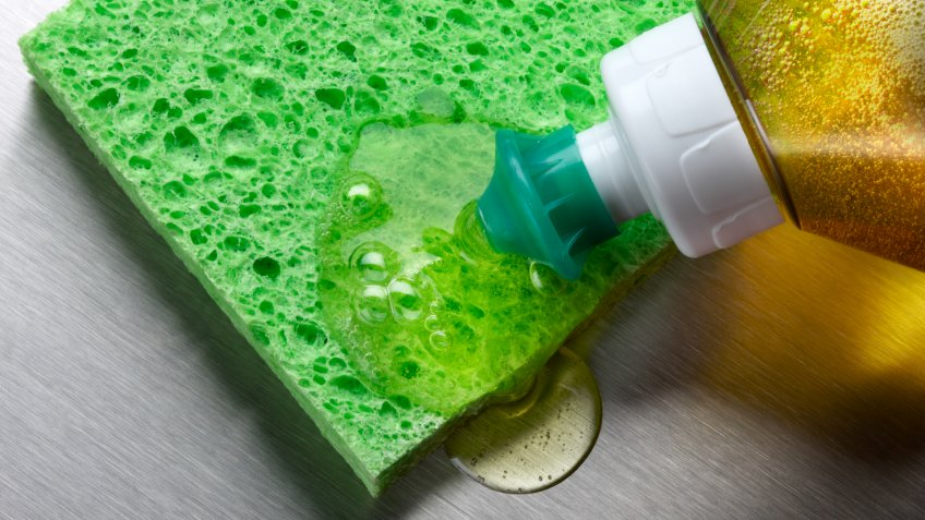 macro shot of dish soap being squeezed onto green sponge in aluminum sink.