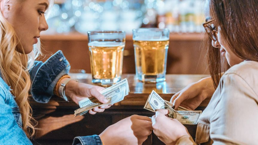 two girls with money paying for drink at bar.