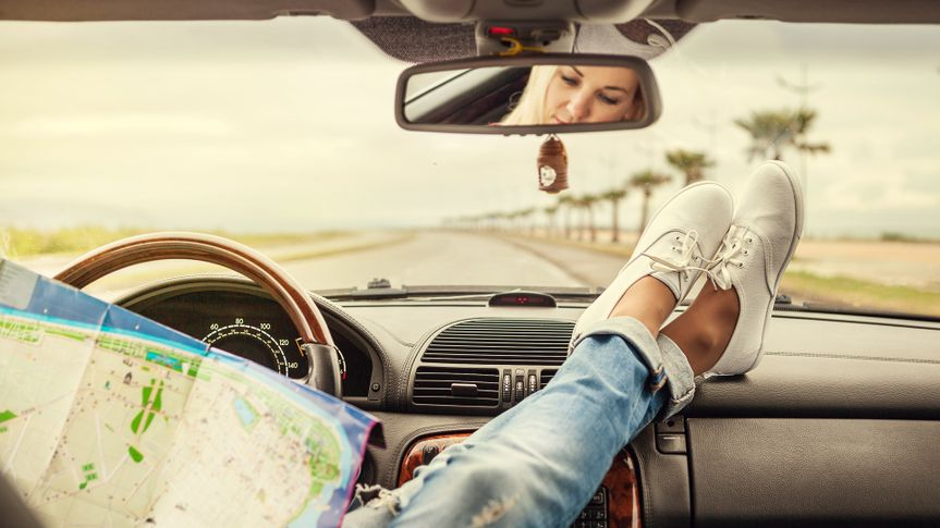 Young woman alone car traveler with map