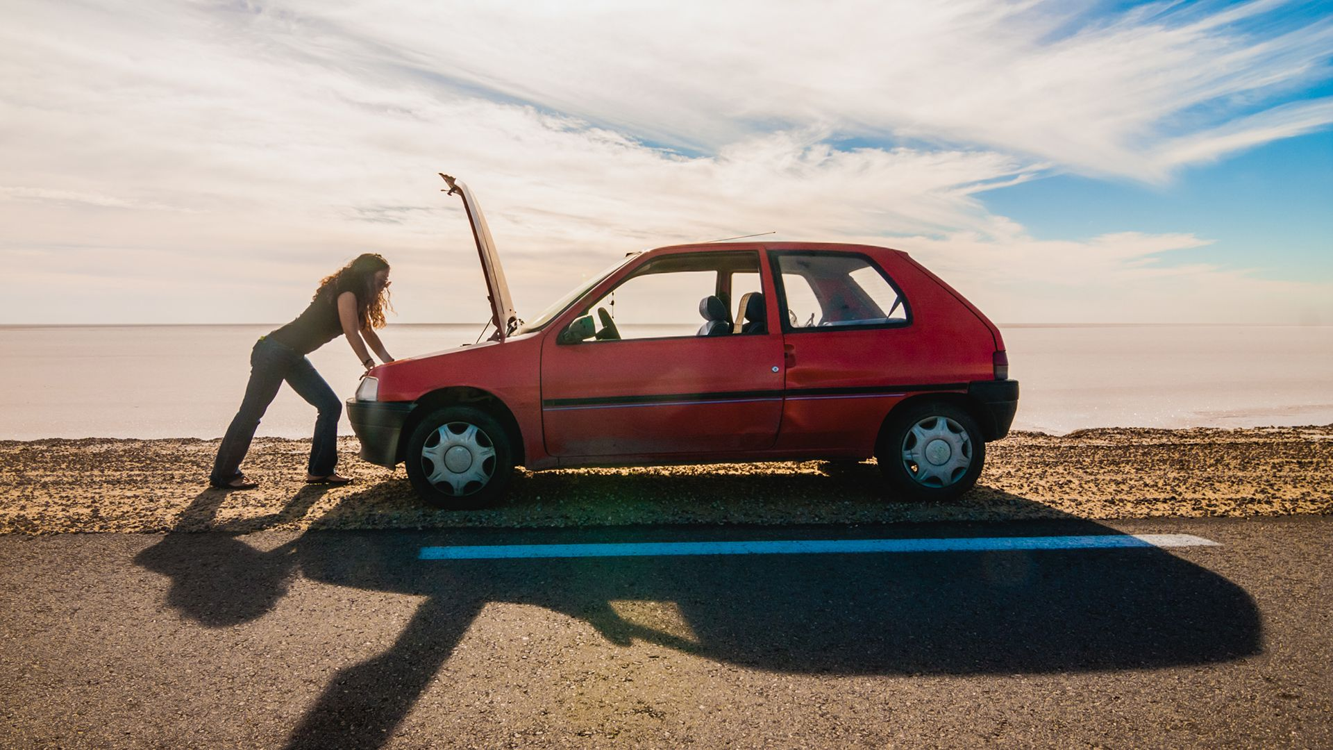 Woman stranded due to car trouble on a desert road.