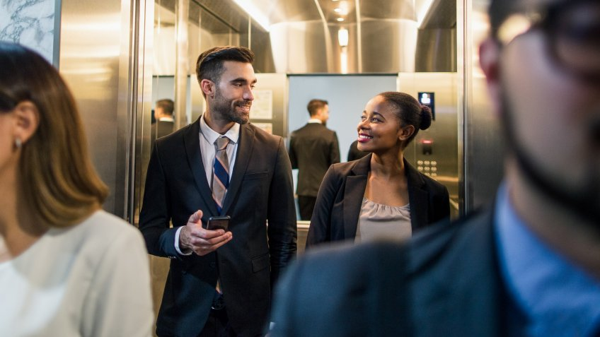 businessman talking with coworker in elevator