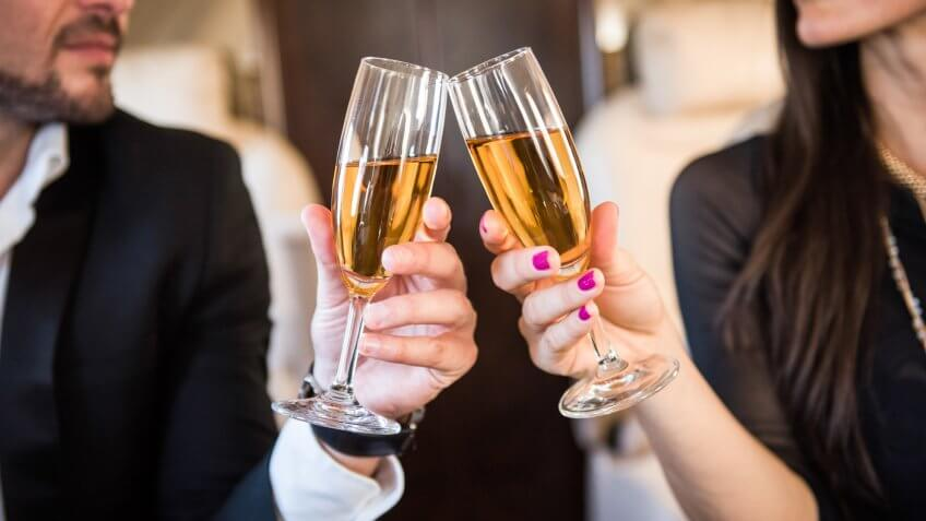 champagne glasses that business couple is holding inside the private jet aeroplane.