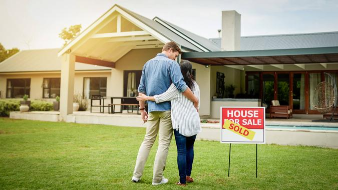 couple admiring their new house with mortgage rates dropping