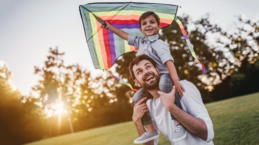 Handsome dad with his little cute sun are having fun with kite on green grassy lawn - Image.