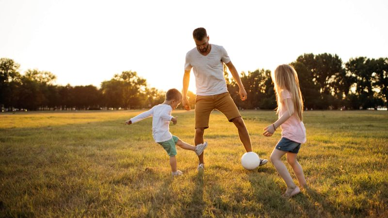 Kids and father playing soccer on a beautiful summer afternoon outdoors.
