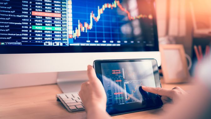 female using tablet looking at stock market chart