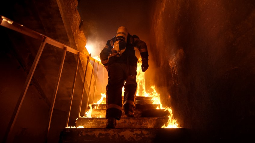firefighter running up the stairs in burning building