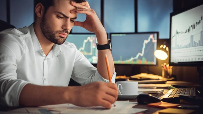 frustrated man with trading charts in background