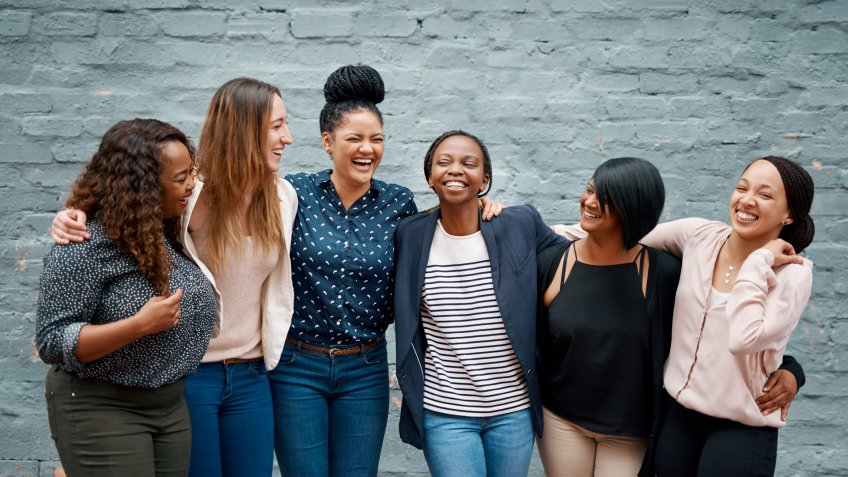 Portrait of a diverse group of young women standing together against a gray wall outside.