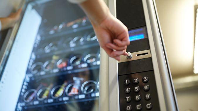 hand pushing button on vending machine