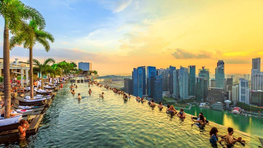 Singapore - May 3, 2018: Infinity Pool at sunset of Skypark that tops the Marina Bay Sands Hotel and Casino from rooftop of La Vie Club Lounge on 57th floor.