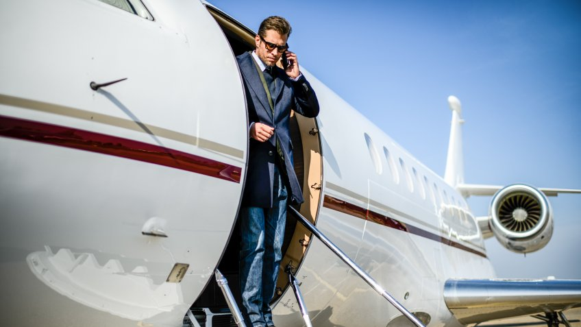 Man wearing elegant clothes exiting the private jet airplane and talking over mobile phone.