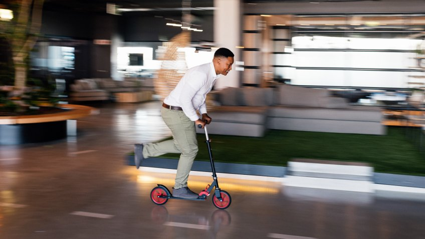 Young African businessman riding scooter inside shared office space.