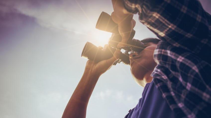 man using binoculars to look in the distance